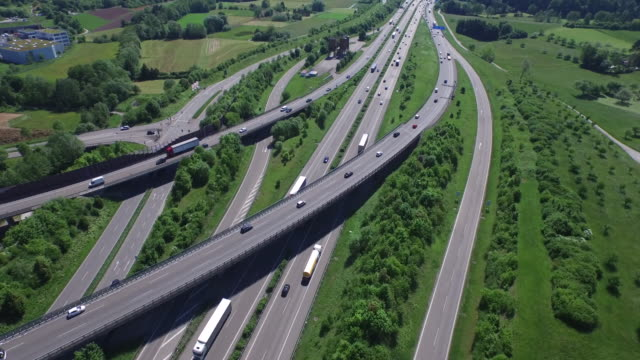 crane shot of vehicles moving on roads and freeways - fernverkehr stock-videos und b-roll-filmmaterial