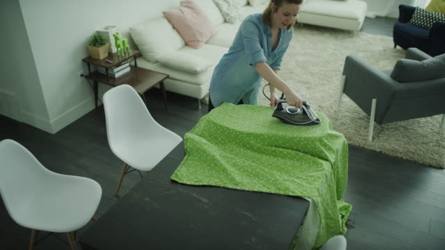 crane shot of woman singing and dancing while ironing fabric / lehi, utah, united states - lehi stock videos & royalty-free footage