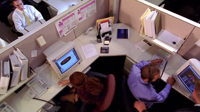 OVERHEAD crane shot office workers talking + working at computers in open office with cubicles