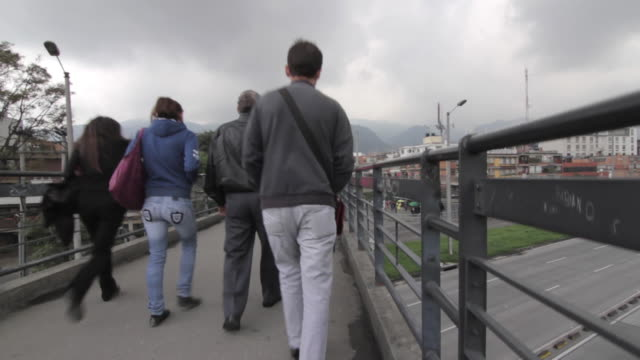 Crane shot over people as they walk along a footbridge in the city Bogota.