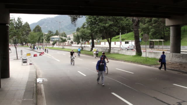 crane shot over people cycling and jogging along a road in the city of bogota. - bogota stock videos & royalty-free footage
