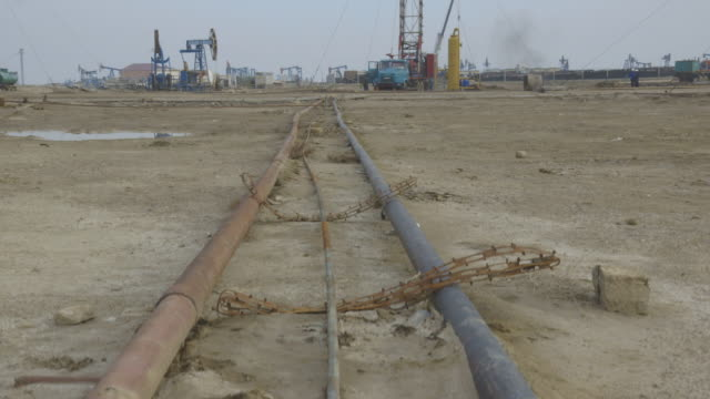 crane shot over pipes at an oil field near baku. - baku video stock e b–roll
