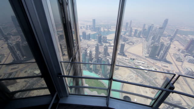 crane shot over the city of dubai from the burj khalifa skyscraper. - schwenk stock-videos und b-roll-filmmaterial
