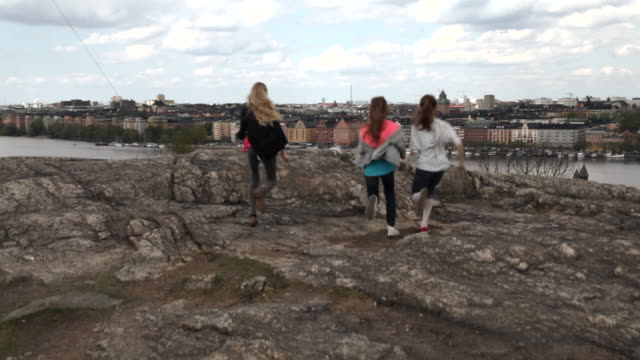 Crane shot over three girls standing on a rocky outcropping, overlooking the city of Stockholm.