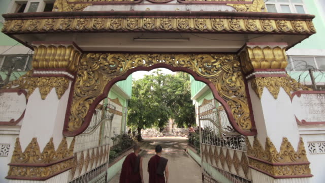 Crane shot over two Buddhist monks as they walk through a decorated archway in Yangon.
