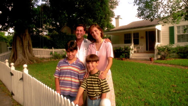 MS crane shot PORTRAIT family posing in front yard of house with white picket fence / Florida