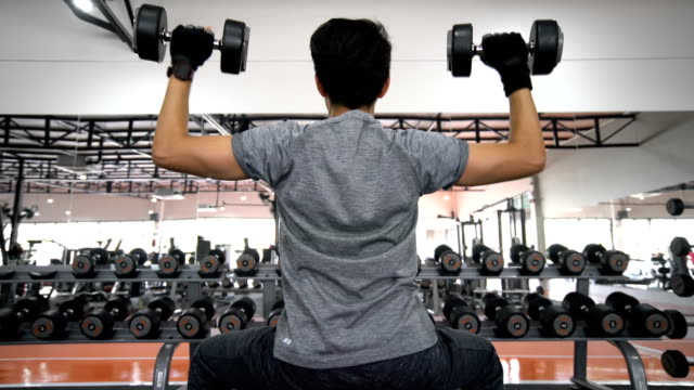 Crane shot rear view of man using dumbbell for building sholuder muscle in gym