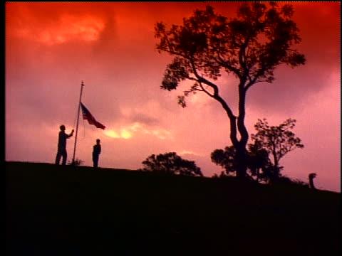 crane shot SILHOUETTE boy saluting on hill as man raises American flag on flagpole / sunrise