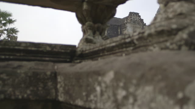 crane shot up a carved stone wall to the angkor wat temple in cambodia.  - cambodia stock videos and b-roll footage