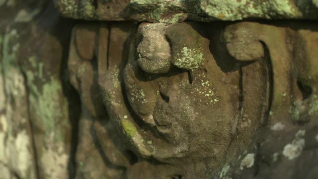 vídeos de stock, filmes e b-roll de crane shot up worn stone carvings decorating the exterior of the bayon temple at angkor.  - exposto ao tempo