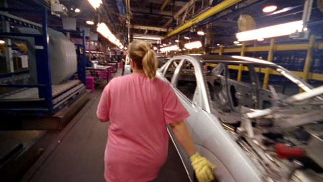crane shot wide shot female factory worker assembling car on assembly line / carrying hood and installing on car - car plant stock videos & royalty-free footage