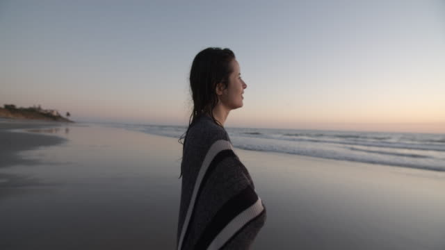 crane shot young woman on the beach at dusk - crane shot stock videos & royalty-free footage