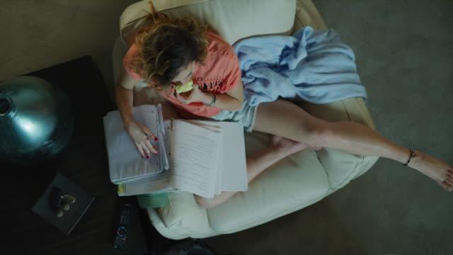 crane shot zoom in to teenage girl doing homework and eating apple / cedar hills, utah, united states - herunterlassen stock-videos und b-roll-filmmaterial