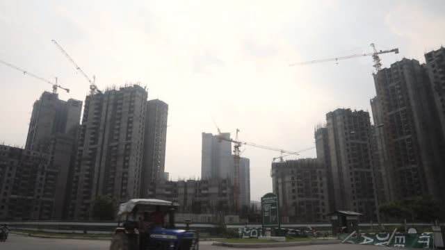 a crane stands in front of residential buildings under construction at the jaypee wish town project developed by jaypee infratech ltd in noida uttar... - uttar pradesh stock videos and b-roll footage