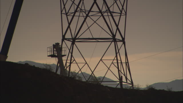 a crane suspends a scaffold as men work on an electrical supply tower. - strom stock-videos und b-roll-filmmaterial