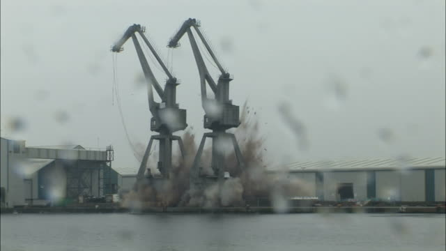 WS Crane towers are demolished using explosives and collapse into  shipping canal  / Liverpool, NorthWest England, UK