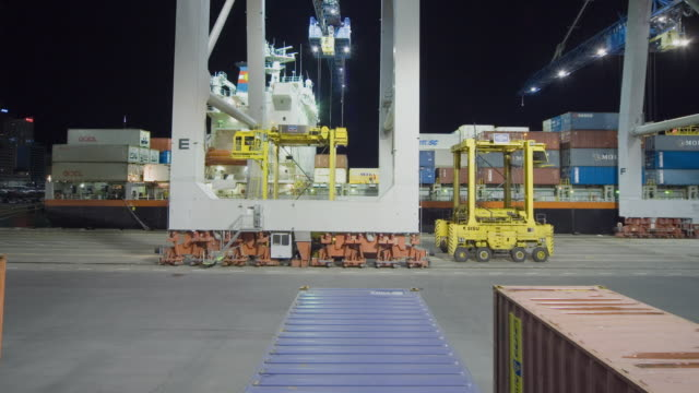 t/l ws crane unloading container ship with help from straddle carriers at ports of auckland/ pov straddle carrier backing over row of container and turning down pathway/ auckland, new zealand - straddle carrier stock videos & royalty-free footage