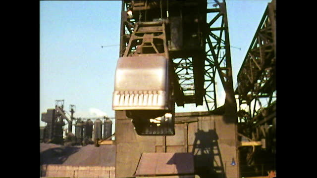 crane unloads metal ore/coal from ship in detroit; 1972 - audio available stock-videos und b-roll-filmmaterial