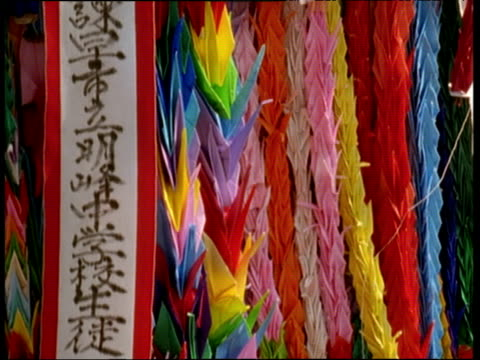 crane up colourful streamers made up of origami cranes hung in remembrance of victims of atomic bomb on 09 aug 45 nagasaki - weapons of mass destruction stock videos & royalty-free footage