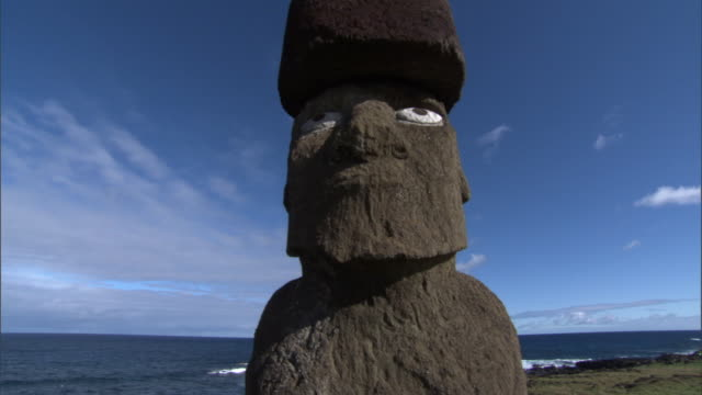Crane up over Moai statue with pukao and eyes, Easter Island