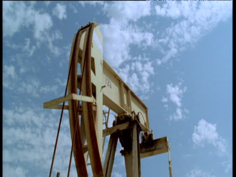 crane up over nodding donkey oil pump in oil field, bakersfield, california - oljepump bildbanksvideor och videomaterial från bakom kulisserna