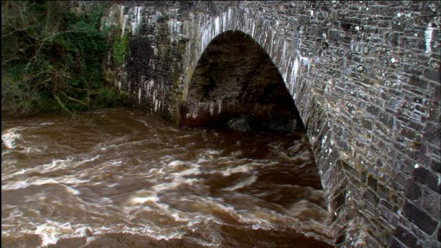 crane up over swollen river flowing under humpback bridge, scotland, uk - flood stock videos & royalty-free footage