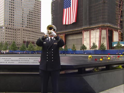 vidéos et rushes de crane up shot of a bugler playing taps at the 9-11 memorial on the morning of 9/11/11. the names of victims in the world trade center attacks were... - mémorial