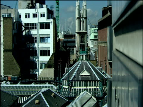 vídeos de stock e filmes b-roll de crane up side of building to view over st. paul's cathedral rooftops and cranes city of london - spire