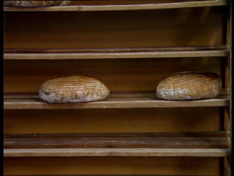 crane up wooden shelves stacked with loaves of bread - bakery stock videos and b-roll footage