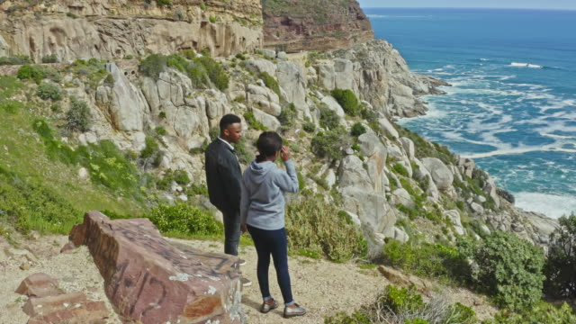 Crane video of young African couple looking at the ocean