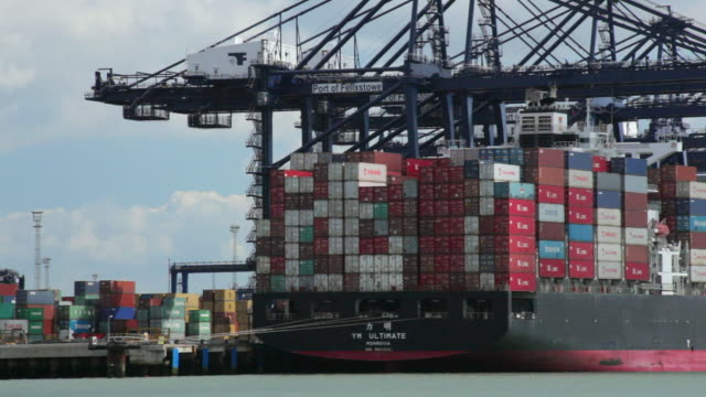 ws pan cranes and container ships at felixstowe dockside / felixstowe, suffolk, uk - scrittura occidentale video stock e b–roll