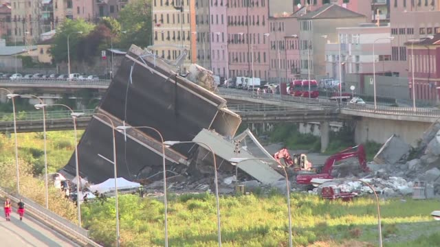 cranes and excavators continue to clear rubble from the collapsed bridge in genoa northern italy despite finding no one last night according to the... - baufahrzeug stock-videos und b-roll-filmmaterial