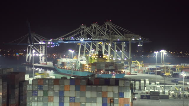 vídeos y material grabado en eventos de stock de tl ha ws cranes and straddle carriers unloading container ship at night at fergusson terminal at ports of auckland/ auckland, new zealand  - pórtico automotor