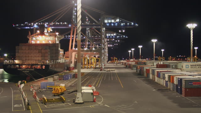 vídeos y material grabado en eventos de stock de tl ha ws cranes and straddle carriers unloading container ship over twelve hour period from night to day at ports of auckland/ auckland, new zealand  - pórtico automotor