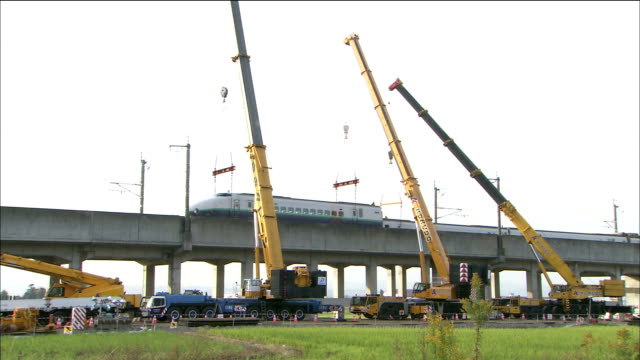 cranes hold the engine of a high-speed train derailed during the chuetsu earthquake. - 脱線点の映像素材/bロール