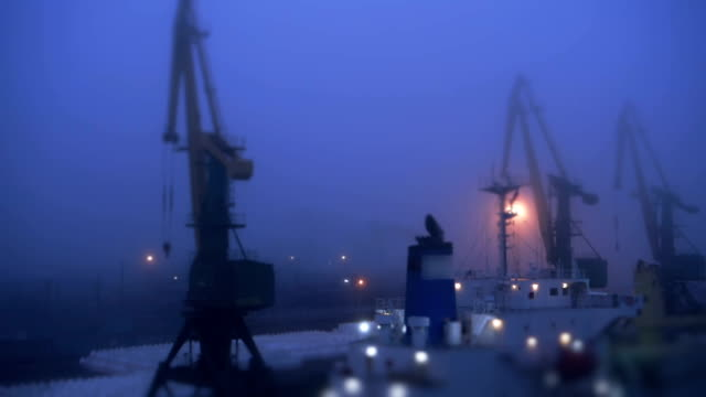 Cranes in commercial dock during foggy weather