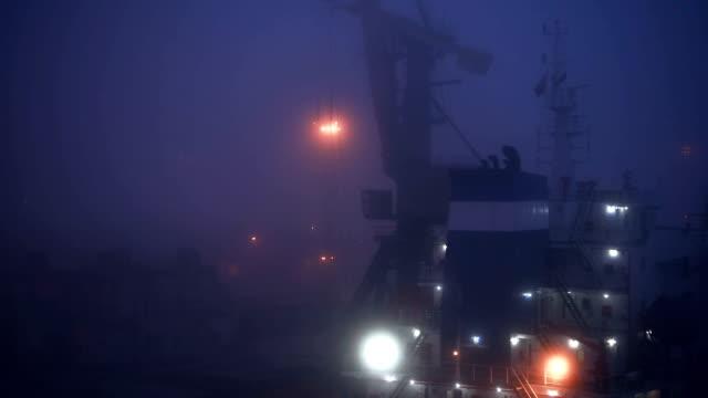 霧の中に商業ドックのクレーン - サーチライト点の映像素材/bロール