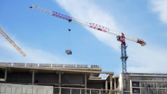 cranes in construction site with blue sky background - crane stock videos & royalty-free footage