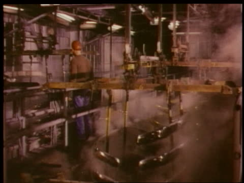 1951 cranes lifting chrome bumpers from steam in Chevrolet factory