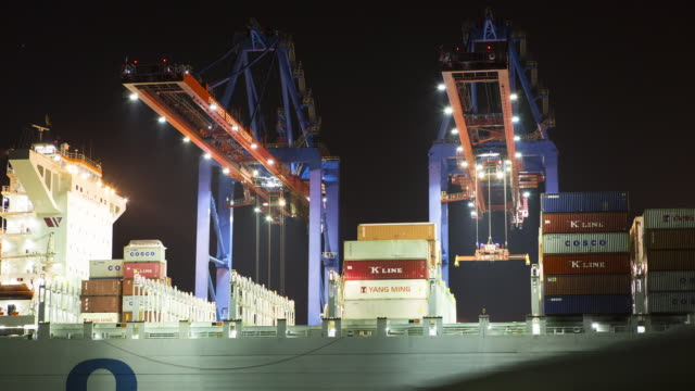 2 Cranes loading freighter ship at night time