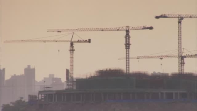 cranes loom over buildings under construction. - crane stock videos & royalty-free footage