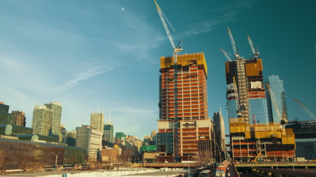 cranes moves around on a construction side new york city - crane stock videos & royalty-free footage