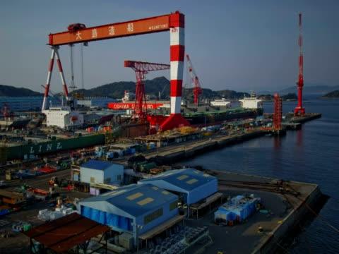 vídeos de stock, filmes e b-roll de t/l cranes moving in the oshima shipyard, oshima, japan - moving activity
