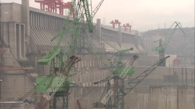 ws zo cranes moving slowly above construction site at three gorges dam / hubei province, china - dam stock videos & royalty-free footage