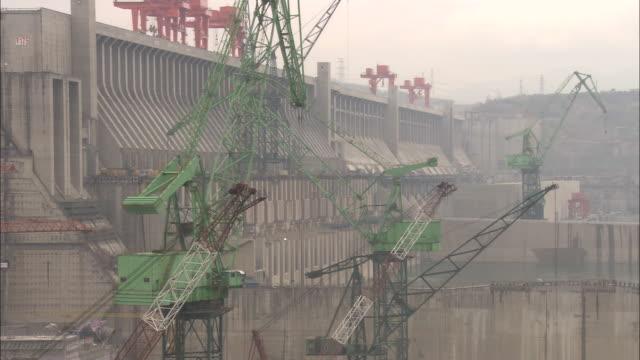 stockvideo's en b-roll-footage met ws zo cranes moving slowly above construction site at three gorges dam / hubei province, china - dam mens gemaakte bouwwerken