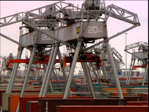 cranes of rotterdam shipping port crane lifts container moves left out of picture - schiffsfracht stock-videos und b-roll-filmmaterial