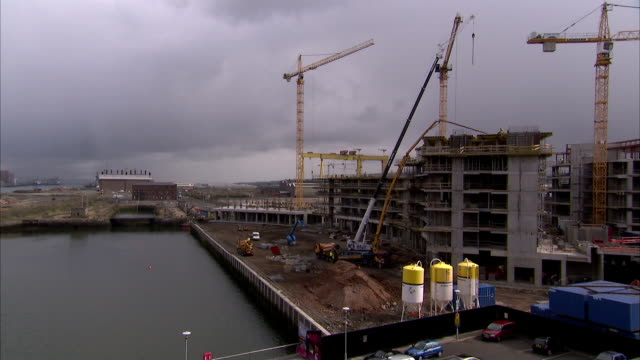 cranes stand on a construction site with the historic harland and wolff and paint hall buildings in the distance, belfast's titanic quarter. available in hd. - titanic belfast stock videos & royalty-free footage