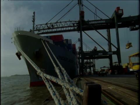 vídeos de stock e filmes b-roll de cranes unload cargo from container ship onto lorries at port felixstowe - engenharia