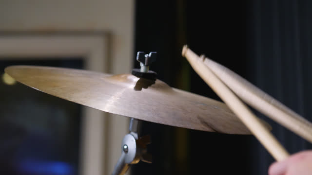 vidéos et rushes de a crash cymbal vibrates in slow motion after being hit on a drum kit - drummer