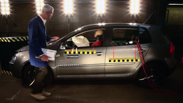 WS Crash test dummy on airbag in smoking crash test car, technician inspecting car / Berlin, Germany